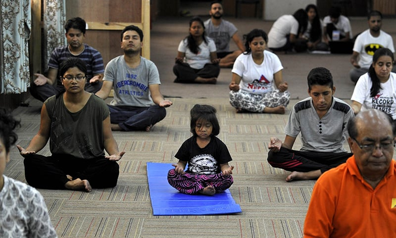 Nepalese people take part in a yoga session to mark International Yoga Day in Kathmandu. ─ AFP