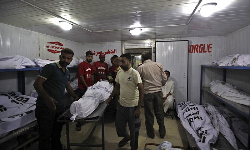 Men move the body of a deceased, who died due to intense hot weather, at Edhi morgue.- Reuters