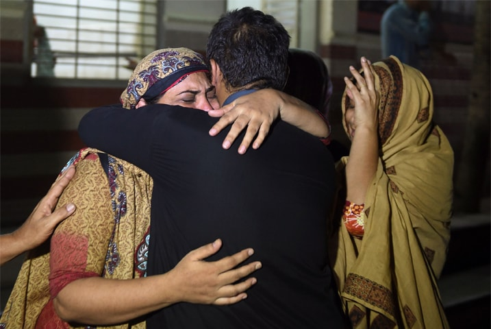 KARACHI: Relatives mourn the death of a heatstroke victim at an Edhi morgue on Sunday.—AFP
