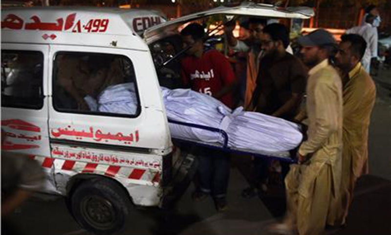 EDHI volunteers and relatives shift the dead body of a heatwave victim into an ambulance at the EDHI morgue.—AFP