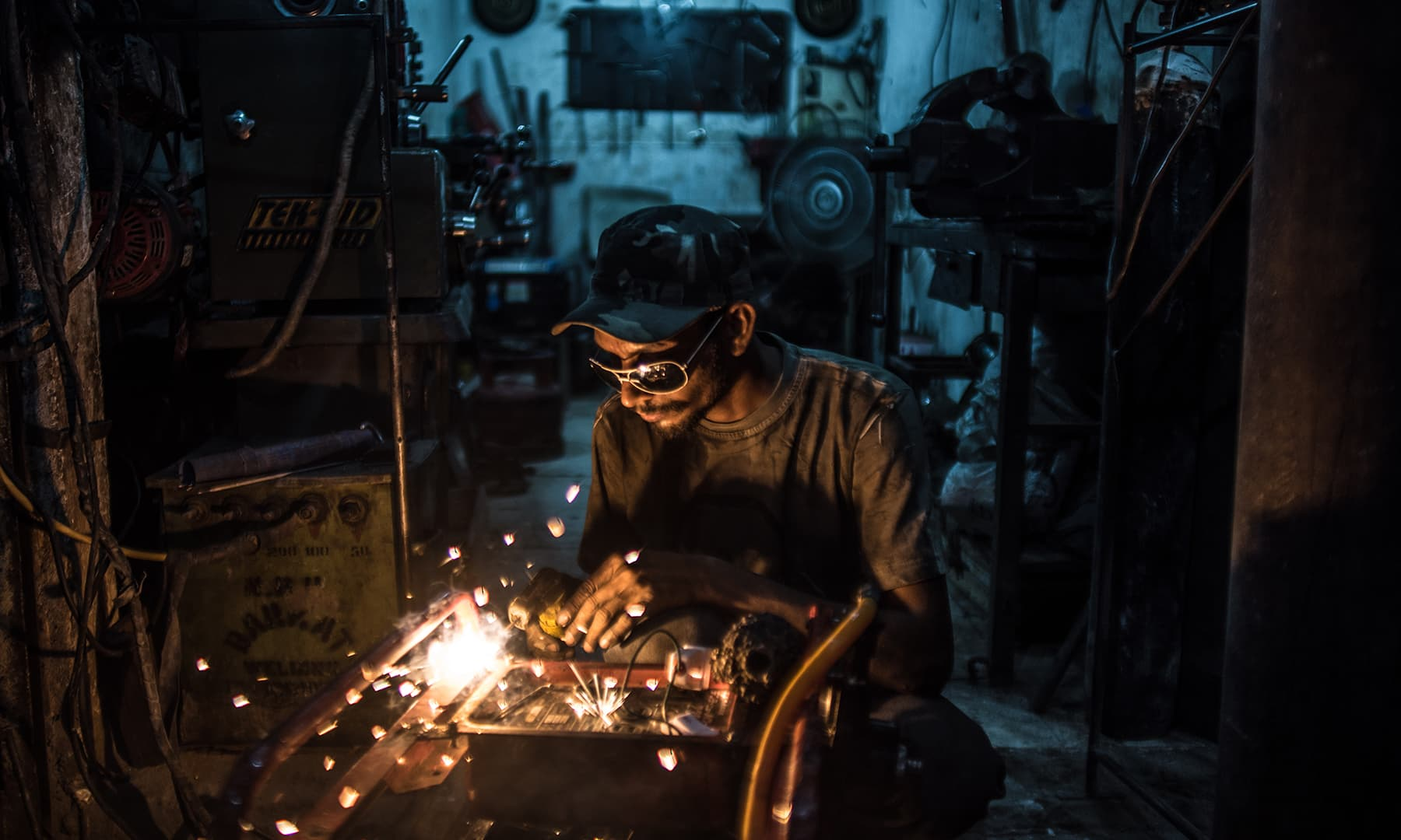 A mechanic's apprentice at work in a shop near UP Morr, Karachi