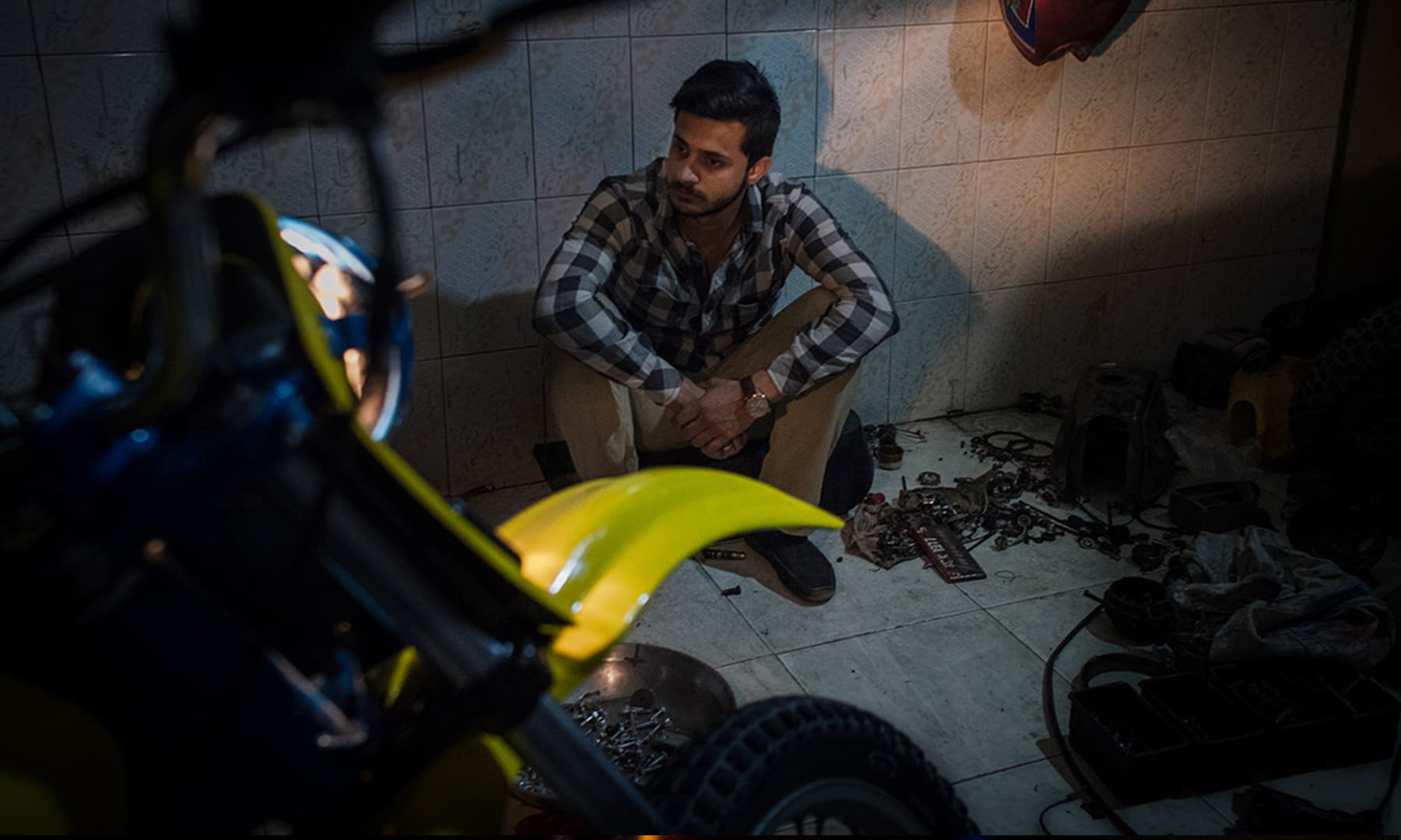 A biker watches as his motorcycle is upgraded at a mechanic's shop