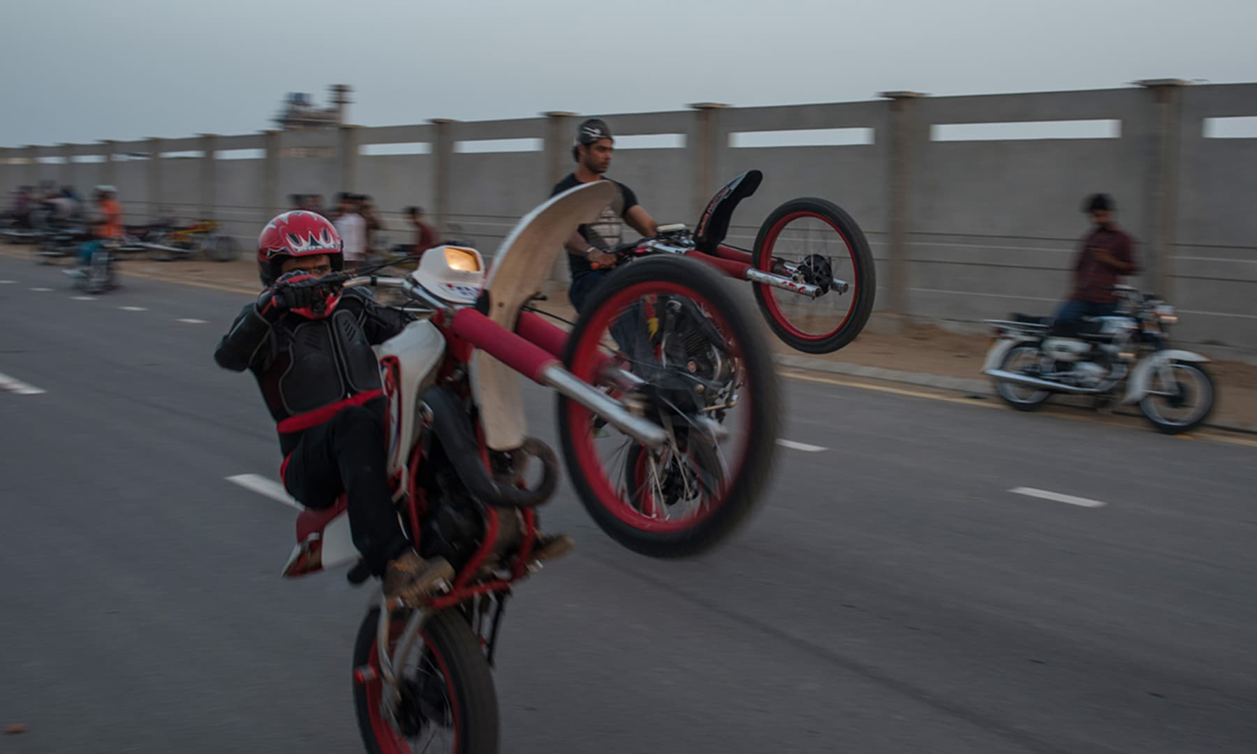 Two bikers show off their skills near Seaview, Karachi