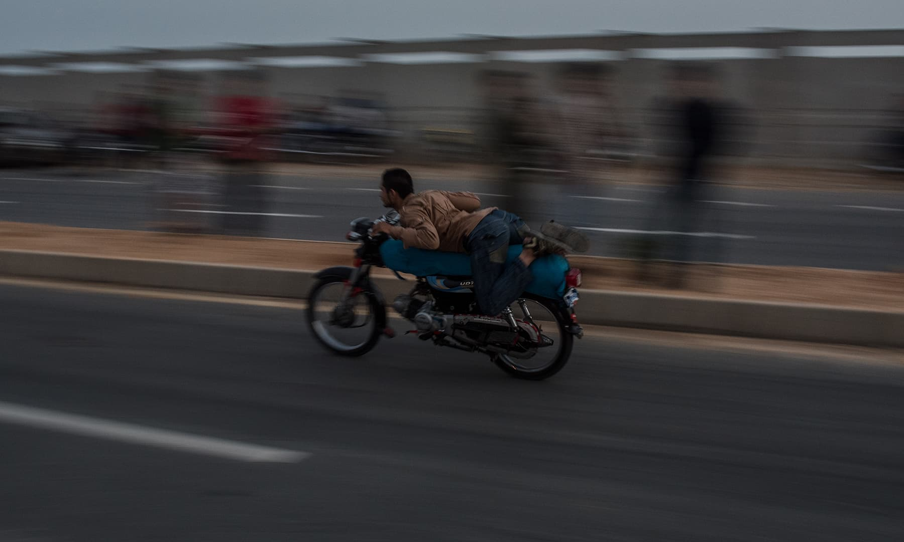 A biker lies flat on his motorcycle as he glides past spectators