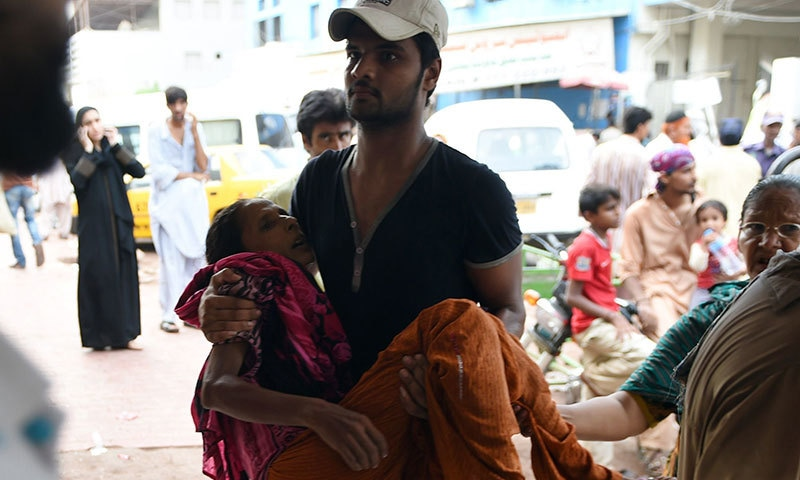 A man carries a heatwave victim to a hospital in Karachi on June 22, 2015.—AFP