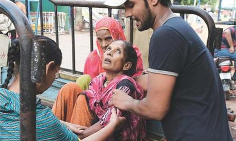 A man brings a heat wave victim to a hospital in Karachi. — AFP