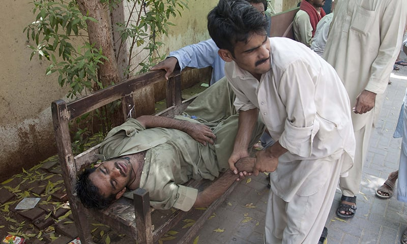 A man tries to help another who has fainted due to the heat at a roadside in Karachi. - AP