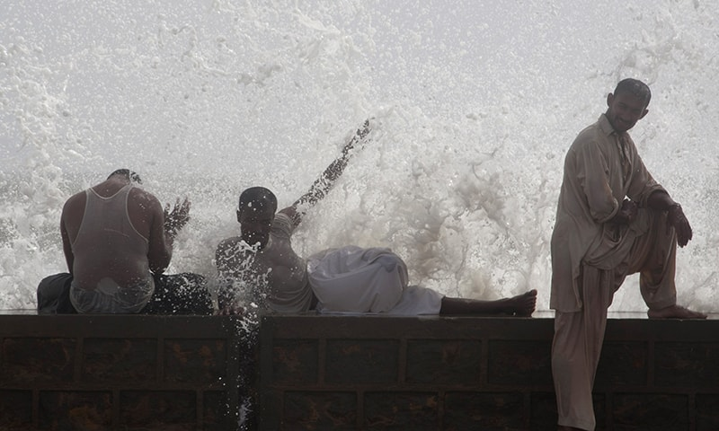 People cool themselves off at Sea View in Karachi on Tuesday. - AP