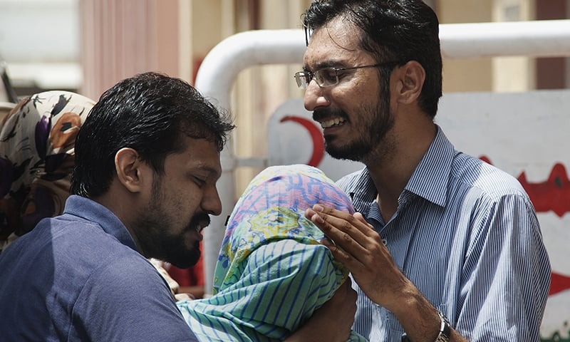 Family members comfort a woman who lost her husband due to heatstroke in Karachi. ─ AP/File