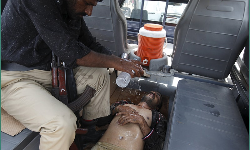 A policeman sprinkles water on a colleague, who collapsed due to the heat, in a police van outside Jinnah Postgraduate Medical Centre (JPMC) in Karachi. ─ Reuters