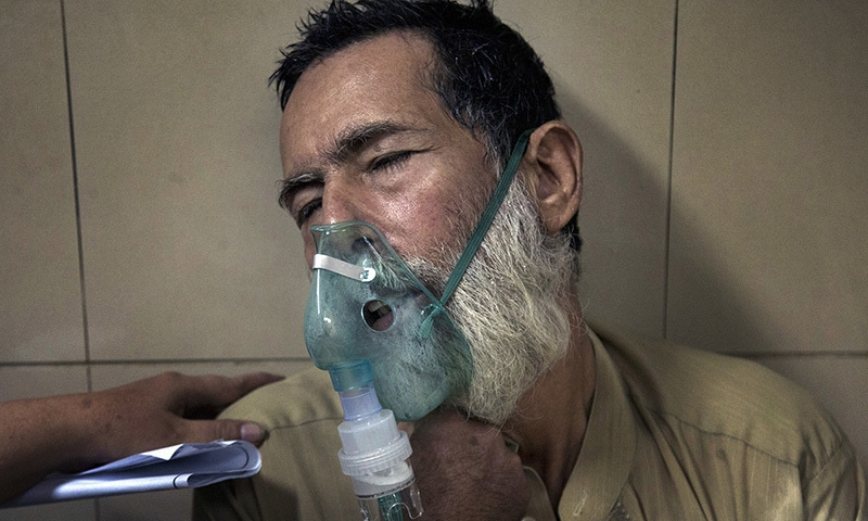 A patient suffering from a heatstroke receives treatment at a local hospital in Karachi. ─ AP
