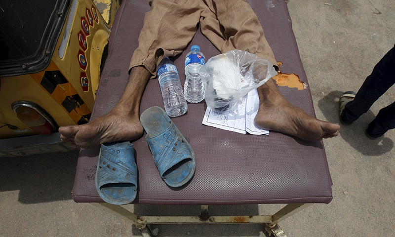 A man, who collapsed due to the heat, lies on a stretcher with his belongings of sandals and water bottles, outside Jinnah Postgraduate Medical Centre (JPMC) in Karachi. ─ Reuters