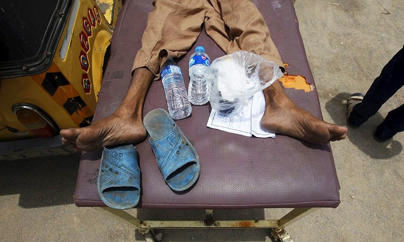 A man, who collapsed due to the heat, lies on a stretcher with his belongings of sandals and water bottles, outside Jinnah Postgraduate Medical Centre (JPMC) in Karachi. —Reuters