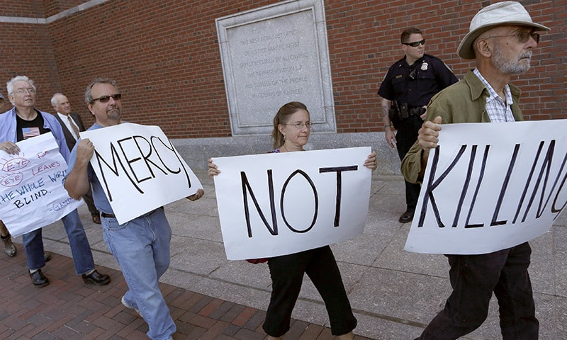 Protesters against the death penalty walk with signs before the formal sentencing of convicted Boston Marathon bomber Dzhokhar Tsarnaev at the federal courthouse in Boston, Massachusetts June 24, 2015. —Reuters