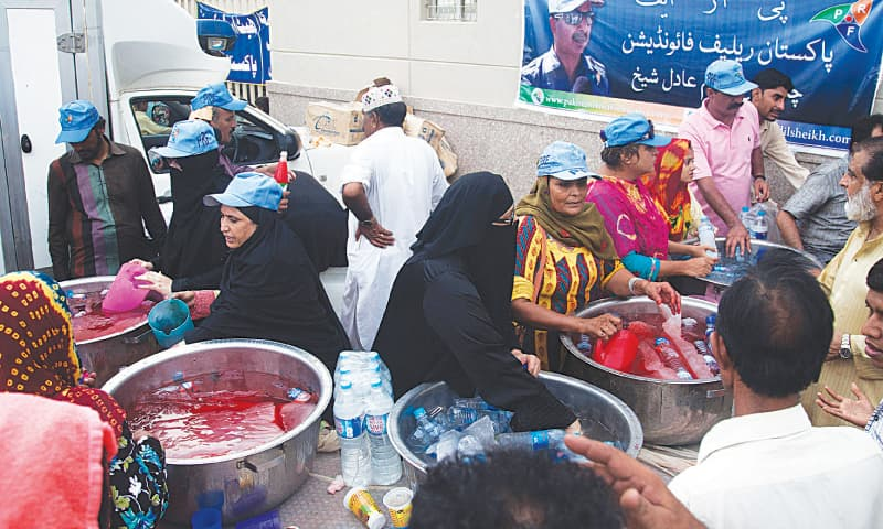 Volunteers provide cold water and soft drinks to people affected by the heatwave in Karachi.—AP