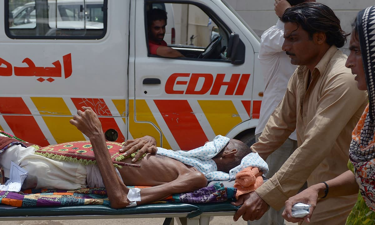 Relatives bring a heatstroke victim to a hospital in Karachi. —AFP