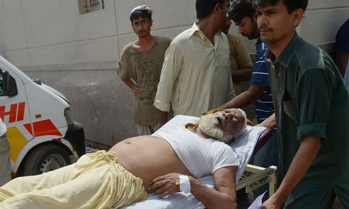 An old man suffering from heatstroke is brought to a hopistal Karachi. —AFP