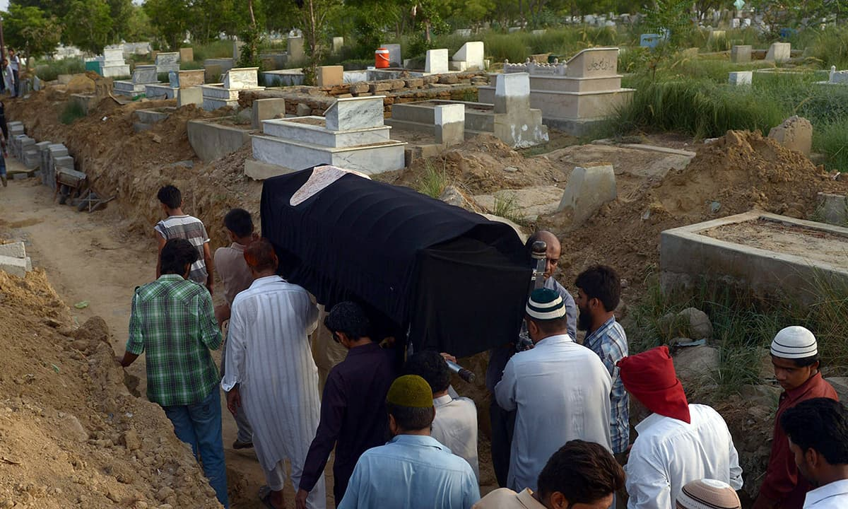 Relatives prepare to bury a heatstroke victim at a graveyard in Karachi. —AFP