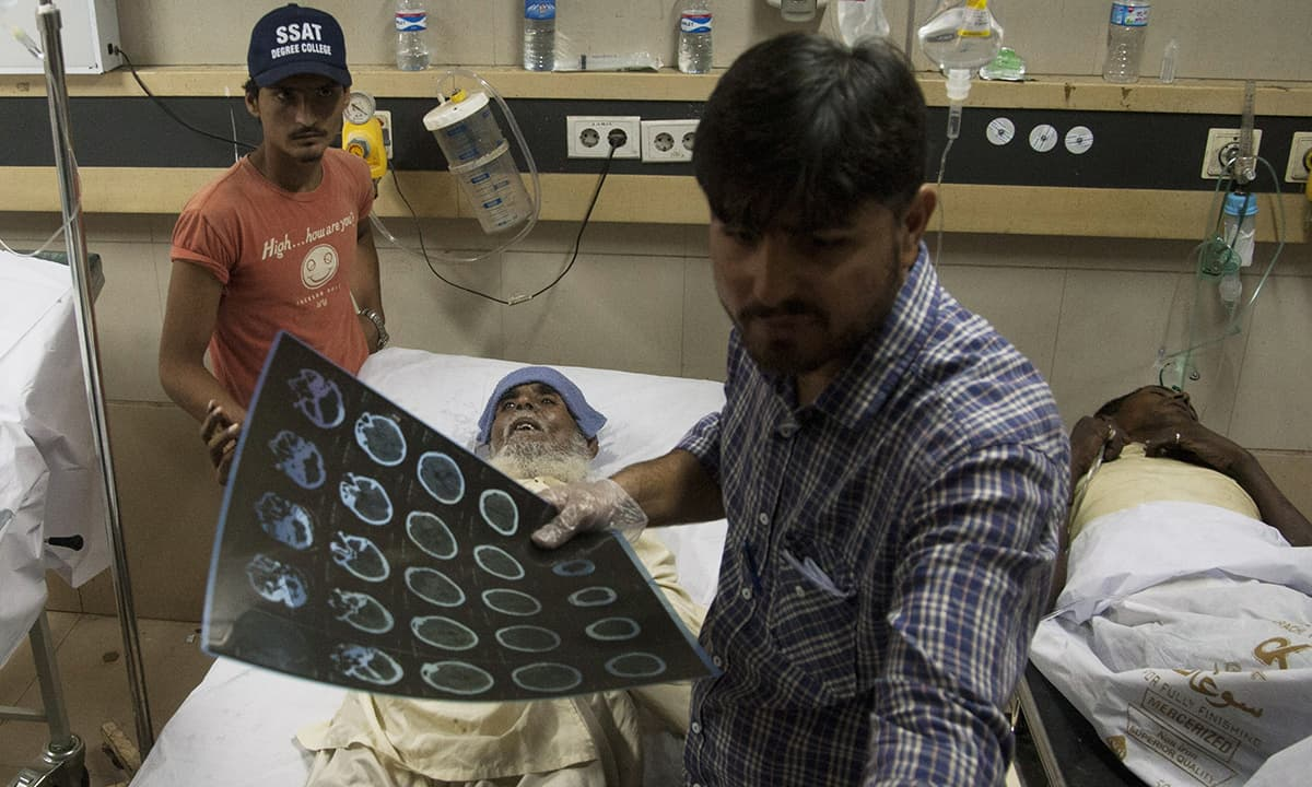 A doctor treats a heatstroke victim at an emergency ward of a hospital in Karachi. —AP