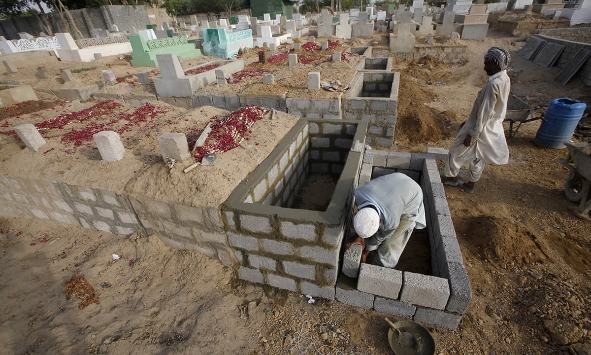 Labourers build mass graves to bury victims of the intense heatwave in Karachi. —Reuters