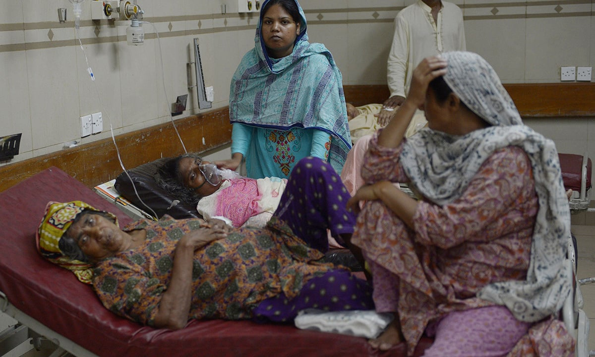 Relatives tend to heatstroke victims as they are treated at a government hospital in Karachi. —AFP