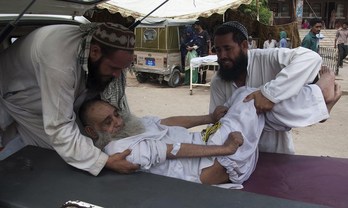 Family members bring an elderly person to a hospital suffering from a heatstroke in Karachi. —AP