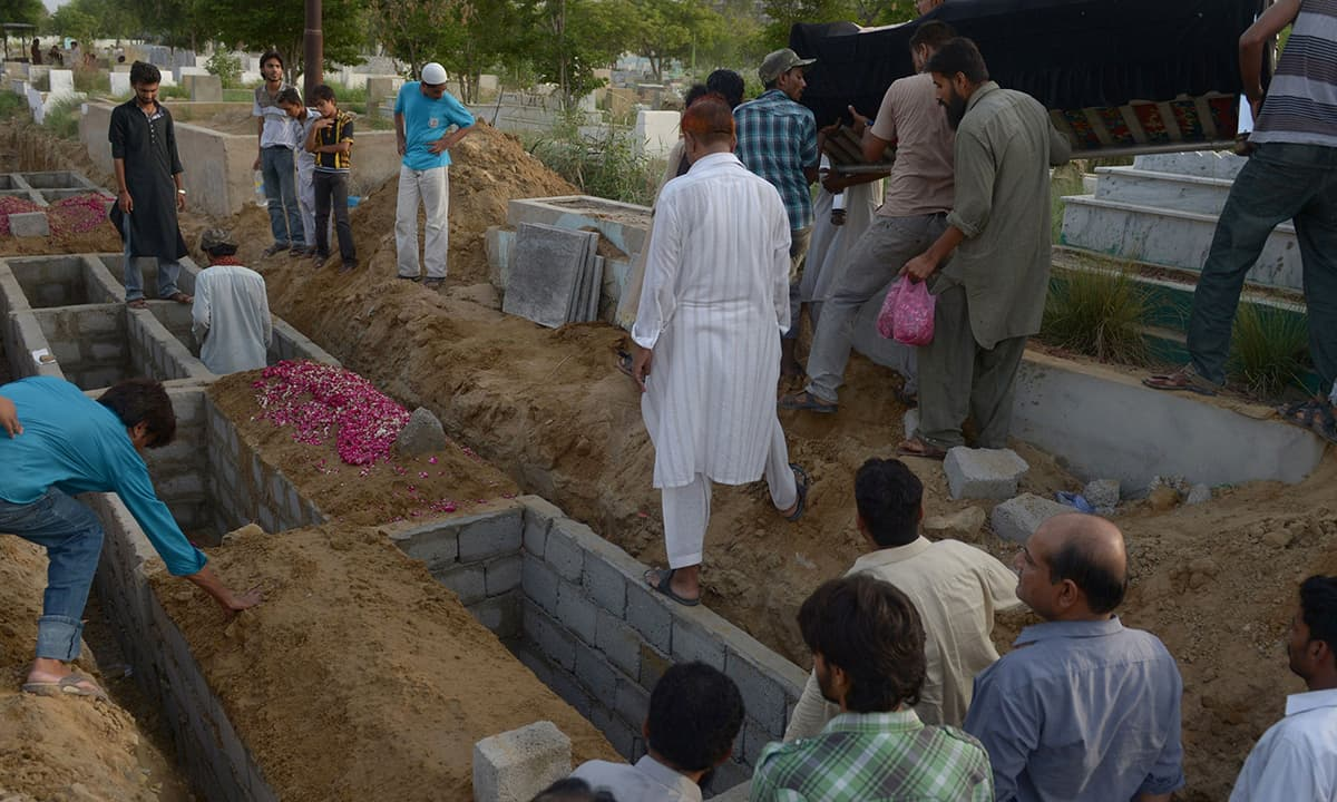 Relatives prepare to bury a victim of heatstroke at a graveyard in Karachi. —AFP