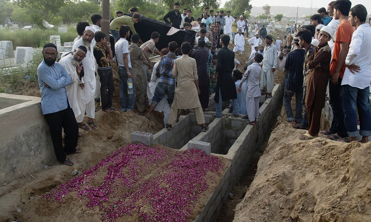 People bury a person who lost his life due to extreme weather in Karachi.—AP