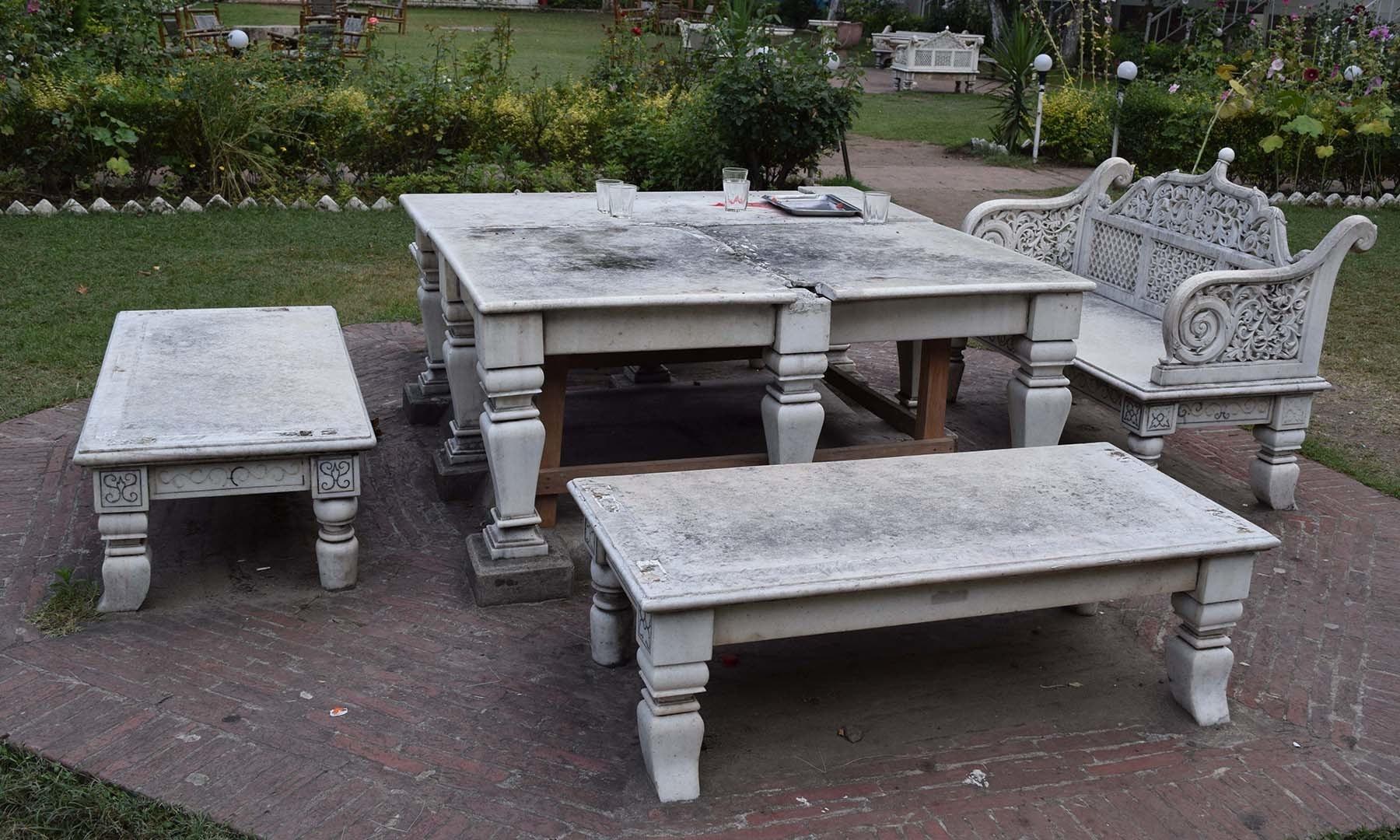 سفید محل کے صحن میں سفید ماربل سے تعمیر شدہ میز اور کرسیوں کا منظر۔