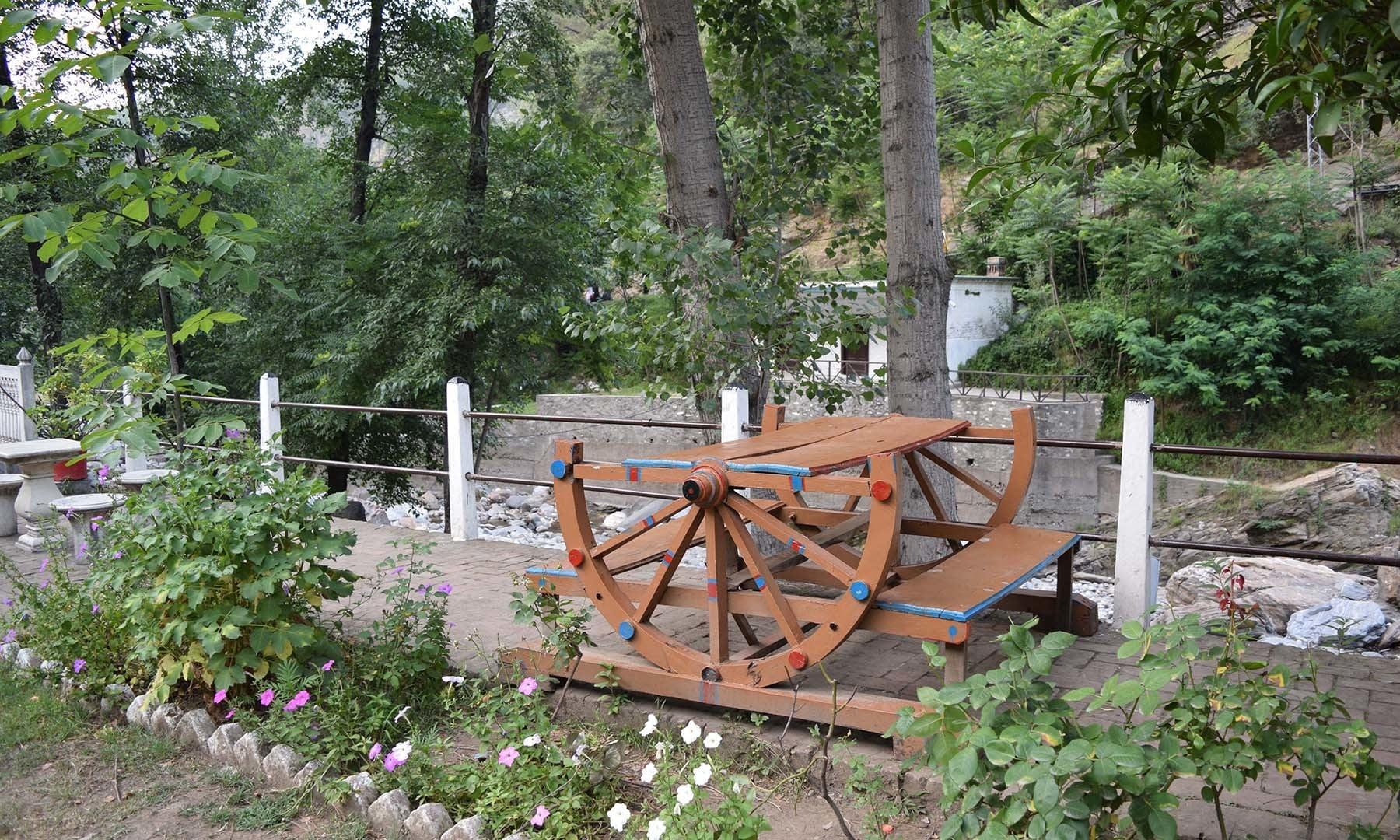 سفید محل کے صحن میں تانگے کے پہیوں سے بنی میز اور کرسیوں کا ایک فن پارہ۔