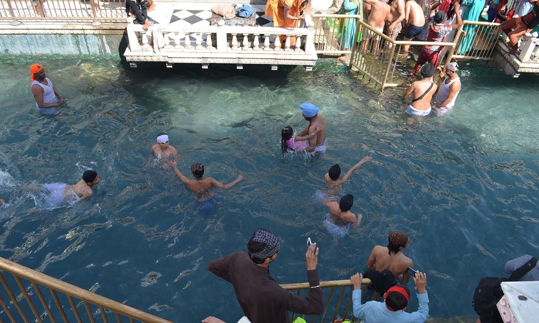 Sikh pilgrims bathing in the holy water at Punja Sahib.