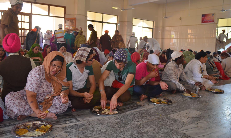 Sikh pilgrims eat 'langer'.