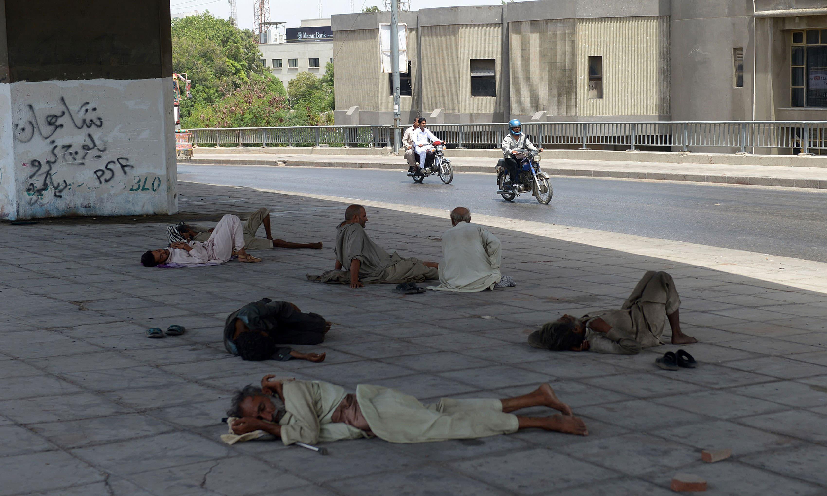 Men rest under a bridge during a heatwave in Karachi on June 29, 2015.– AFP