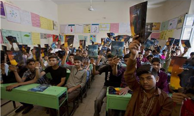 In Lahore, students raise up their copies of the comic books — AP