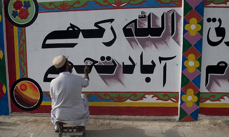 """In this photo taken Thursday, June 4, 2015, a calligraphist paints, """"God bless you,"""" in Urdu over violent graffiti on the wall of an apartment complex and offices after getting permission in Karachi, Pakistan. — AP"""