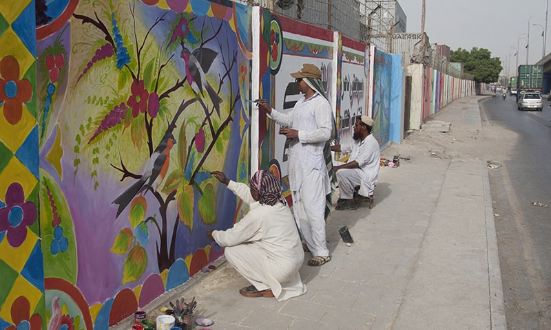 In this photo taken Thursday, June 4, 2015, local artists paint over violent graffiti on the wall of an apartment complex and offices after getting permission in Karachi, Pakistan. — AP