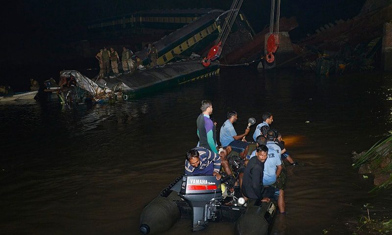 Pakistani rescue workers search for victims after a train carrying soldiers and military hardware fell into a canal following the partial collapse of a bridge in Wazirabad in the Punjab province on July 2, 2015. -AFP