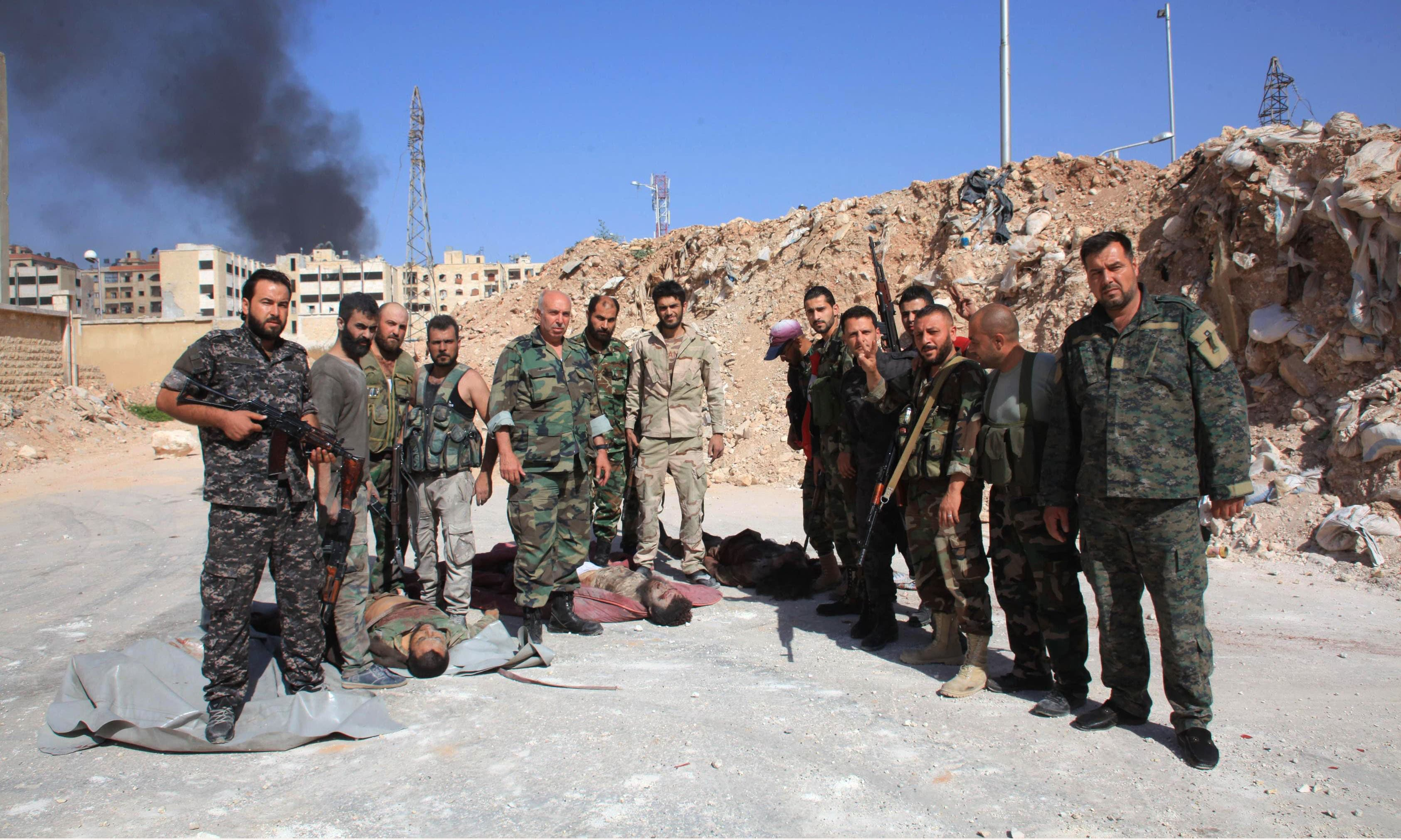 Soldiers from the Syrian government forces pose for a photo next to bodies reportedly of Islamic State (IS) group fighters in the northern Syrian city of Aleppo. —AFP