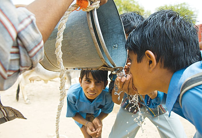 Keeping hydrated: On their way home from school, Thari boys gather to quench their thirst from a bucket of water, Photo by Daniel Bachhuber