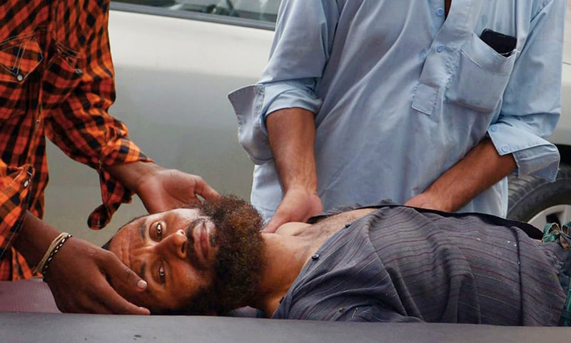 Relatives of a heatstroke victim bring him to a hospital in Karachi on June 25, 2015.—AFP