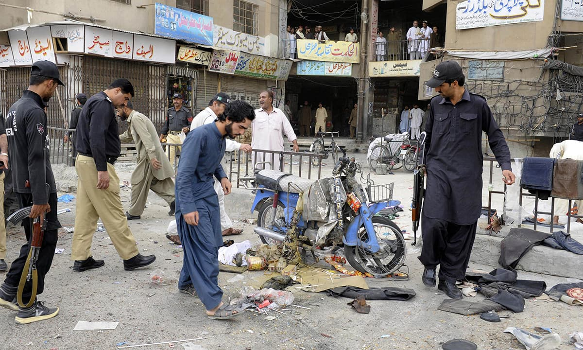 Security personnel gather around the site of a bomb explosion in Quetta's Bacha Khan Chowk on July 5, 2015.–AFP