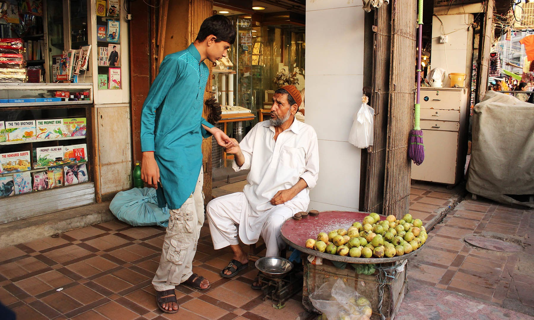 Sabir Chacha guides a boy about keeping change.