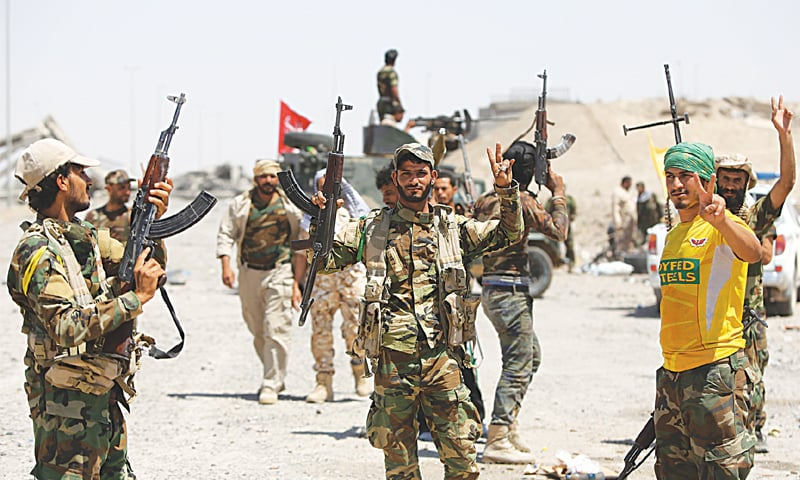 Fallujah: Iraqi fighters from the Popular Mobilisation units supporting the Iraqi government forces flash the sign for victory as they gather on the northern outskirts of the city to prepare an attack on Islamic State group positions in the city on Thursday.—AFP