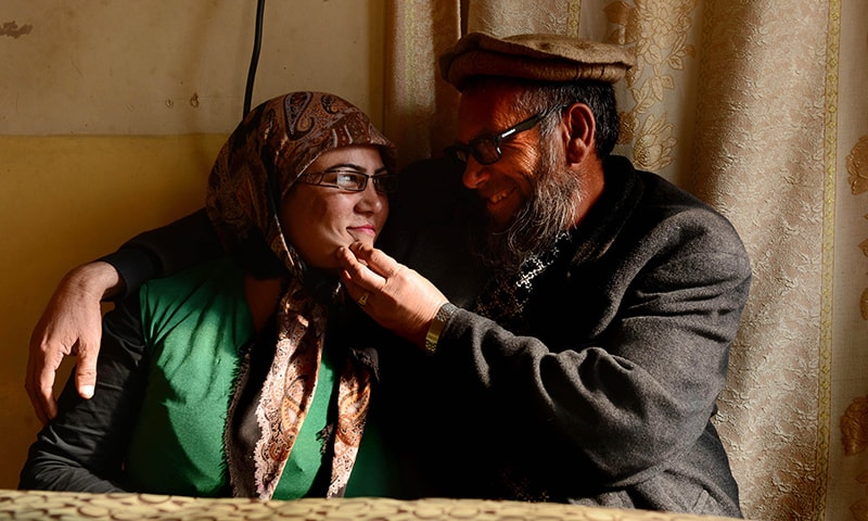 In this file photo taken on February 5, 2015, museum assistant and former Soviet soldier, Sheikh Abdullah, (R), formally known as Bakhretdin Khakimov, who works at the Jihad Museum which contains exhibitions about the Soviet invasion of 1979 and the Afghan resistance, sits with his wife Jamila at a Sandal-e-a table, over a fire and covered with a blanket for warmth, at their home in Herat Province. – AFP/File