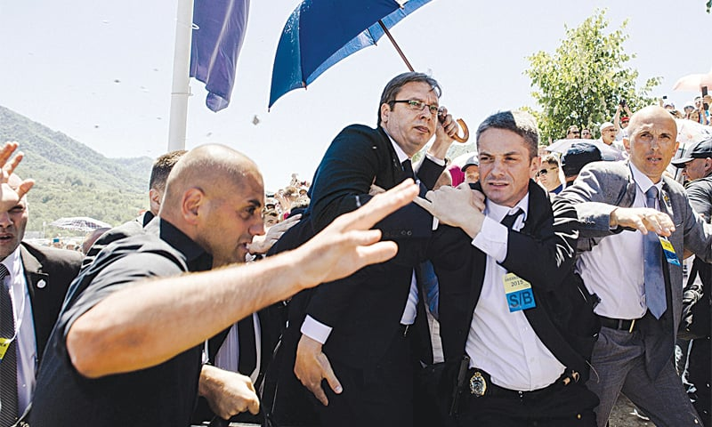 Srebrenica: Bodyguards try to protect Serbian Prime Minister Aleksandar Vucic from stones hurled at him by an angry crowd at the Potocari Memorial Centre, near this eastern Bosnian town. Tens of thousands of people gathered in Srebrenica on Saturday to commemorate the 20th anniversary of the massacre of thousands of Muslims in the worst mass killing in Europe since World War II. The Serbian leader was forced to leave the memorial when the crowd started to chant slogans and throw stones.—AFP