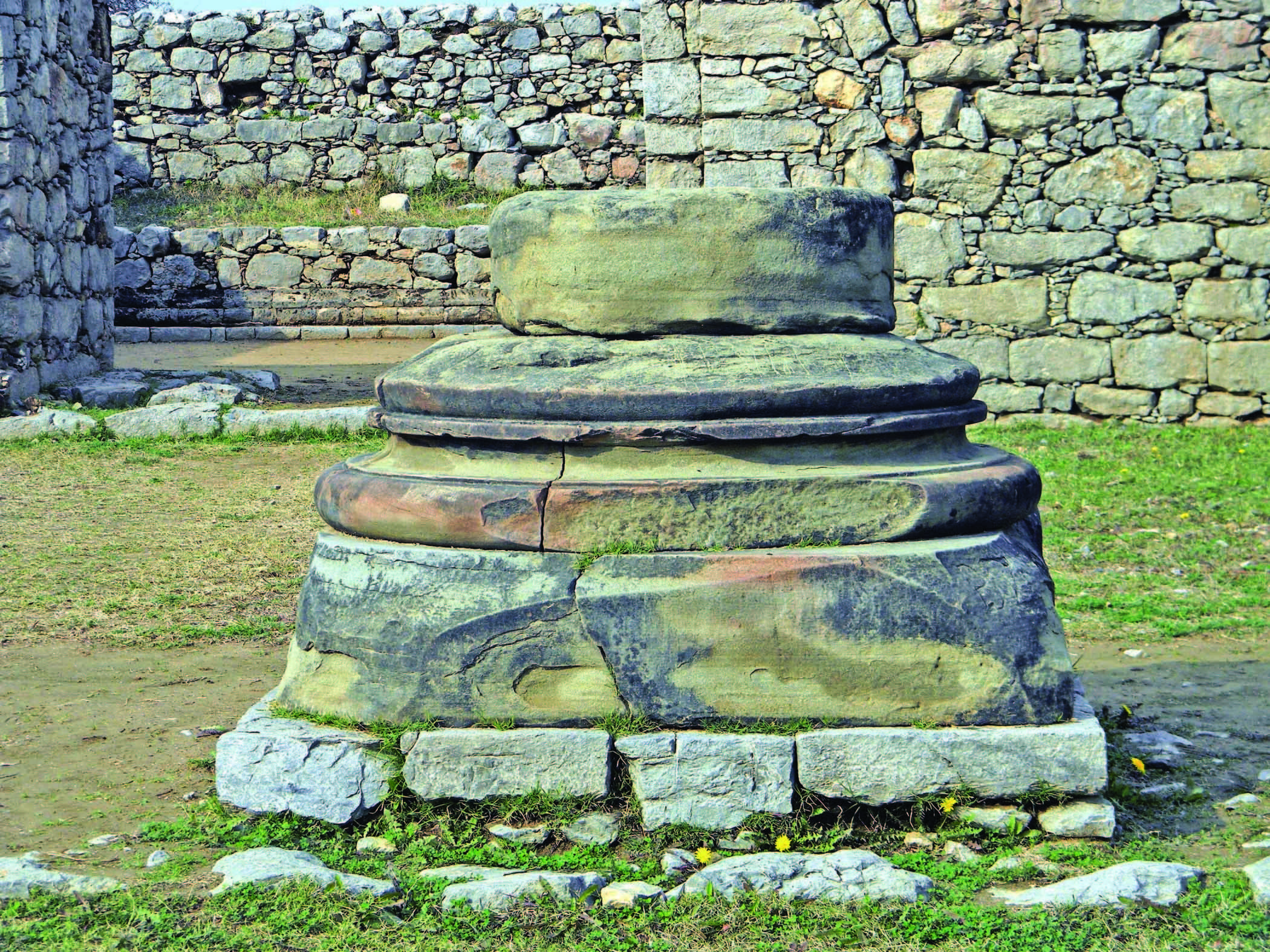 Base of the column of sandstone placed in front of Jandial temple.