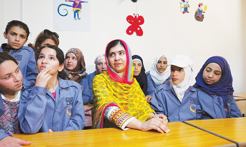 Nobel Peace Prize laureate Malala Yousafzai sits with girls in a classroom at a school for refugee girls built by an NGO in Lebanon's Bekaa Valley on Sunday.—Reuters