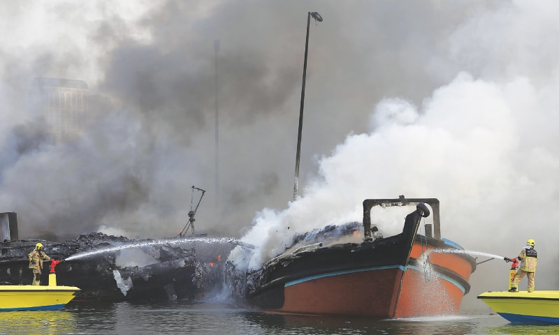 Dubai: Smoke rises from two boats as fire-fighters spray water to extinguish the fire.—AP