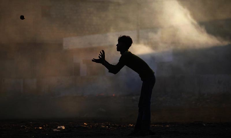A boy is silhouetted against smoke while playing cricket on a street in Karachi. — Reuters