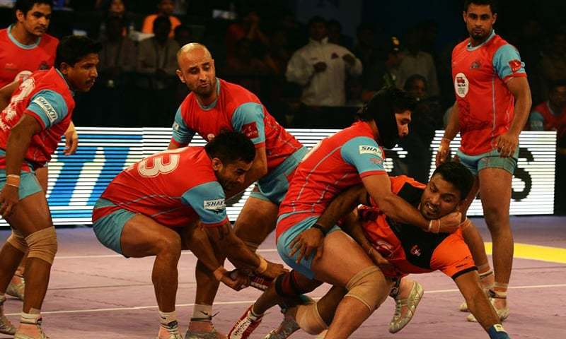 Jaipur Pink Panthers players attempt to tag the U Mumba team raider (R, in orange) during the final match between U Mumba and Jaipur Pink Panthers in the Pro Kabaddi League in Mumbai on August 31, 2014. — AFP/File